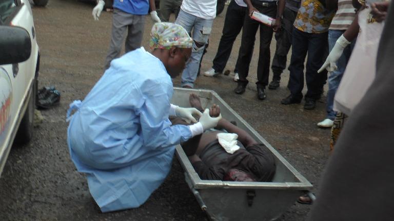 Le médecin légiste examinant la dépouille de l'unique mort officiel dans les locaux du gros bouquet @ gabonactu.com